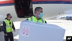 In this photo provided by the Serbian Presidential Press Service, a worker holds a box of the Astra-Zeneca vaccines at Sarajevo Airport, Bosnia, March 2. 2021.