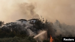 Firefighters spray water to extinguish a fire approaching to a settlement near Cokertme village in Bodrum region, Turkey, August 3, 2021.