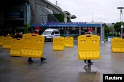 Staff members move barriers in front of a railway station of Wuhan on the first day of inbound train services resumed following the novel coronavirus disease (COVID-19) outbreak, in Wuhan, China, March 28, 2020.