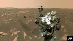 Esta imagen proporcionada por la NASA el 6 de abril de 2021, muestra a la sonda Perseverance en primer plano y al helicóptero Ingenuity unos 3,9 metros detrás.