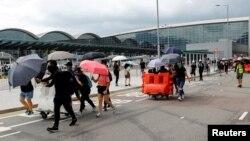 Protesters build barricades outside the terminals at Hong Kong International Airport, in Hong Kong, Sept. 1, 2019.
