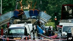 FILE - A double-decker bus blown up by a bomb and damaged cars are scattered at Tavistock Square in London, July 7, 2005. A mixture of homegrown extremists, geography and weak counterterrorism strategies have made Europe a prime target for jihadists.