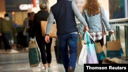 FILE PHOTO: Shoppers carry bags of purchased merchandise at the King of Prussia Mall, United States' largest retail shopping space, in King of Prussia