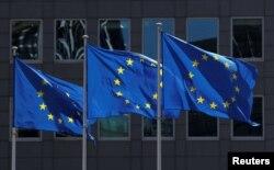 FILE - European Union flags flutter outside the European Commission headquarters in Brussels, Belgium, June 25, 2020.