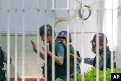 Wartawan Jepang Yuki Kitazumi mengangkat tangannya saat ia dikawal oleh polisi setibanya di kantor polisi Myaynigone di kota Sanchaung di Yangon, Myanmar, 26 Februari 2021. (Foto: AP)