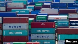 FILE - A truck carrying containers is seen near a Chinese flag at the Yangshan Deep Water Port in Shanghai, China, Aug. 6, 2019.
