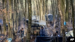 Migrants make shelters from plastic sheets and tree branches at a makeshift camp in a forest outside Velika Kladusa, Bosnia, Jan. 5, 2021.