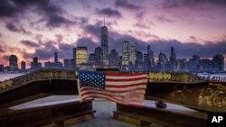 پرچم آمریکا آویخته از تیرآهن آسیب دیده در حملات تروریستی ۱۱ سپتامبر ۲۰۰۱ به مرکز تجارت جهانی در مراسم یادبودی در نیوجرسی در سال ۲۰۱۹.