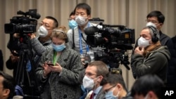 Journalists wearing face masks attend an official press conference about a virus outbreak at the State Council Information Office in Beijing, Sunday, Jan. 26, 2020. The new virus accelerated its spread in China, and the U.S. Consulate in the…