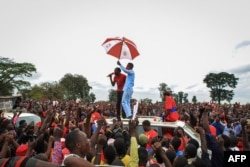 Ugandan musician turned politician Robert Kyagulanyi, also known as Bobi Wine, holds an umbrella as he is introduced to supporters during his presidential rally before being arrested in Luuka, Uganda, Nov. 18, 2020.