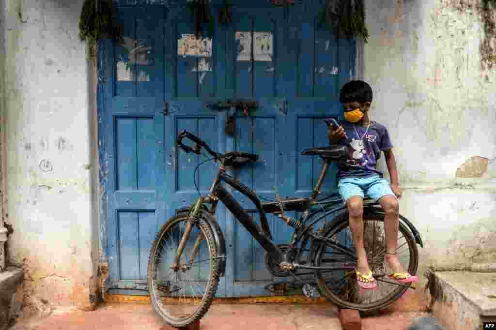 Kijana akiwa amevaa barakoa amekaa mbele ya duka akitumia simu wakati maduka yalipotakiwa kufungwa ili kudhibiti maambukizi ya COVID-19 huko Hyderabad Julai 16, 2020.(Photo by NOAH SEELAM / AFP)