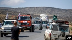 FILE - A convoy of trucks from Doctors Without Borders carrying medical supplies stops by the side of the road after receiving news that the road ahead has been closed by the Ethiopian military, in the Tigray region of northern Ethiopia, May 8, 2021.