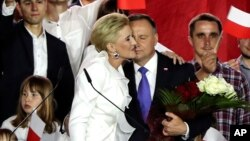 Incumbent President Andrzej Duda is hugged by his wife Agata Kornhauser-Duda in Pultusk, Poland, Sunday, July 12, 2020. An exit poll in Poland's presidential runoff election shows a tight race that is too close to call between the conservative…