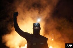 FILE - A protester holds his fist in the air during a protest against racial injustice and police brutality early in the morning on August 23, 2020 in Portland, Oregon.