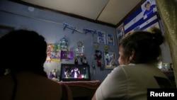 Exiliados nicaragüenses en Costa Rica que huyeron durante las protestas de 2018 observan una transmisión en vivo del discurso del presidente Daniel Ortega en Managua, Nicaragua, el 19 de julio de 2021.