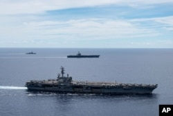 In this photo provided by U.S. Navy, the USS Ronald Reagan (CVN 76, front) and USS Nimitz (CVN 68, rear) Carrier Strike Groups sail together in formation, in the South China Sea, July 6, 2020.