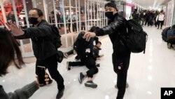 Seorang anggota polisi berbaju preman menyemprotkan semprotan merica ke arah seorang demonstran di sebuah mal yang banyak pedagang China daratan di perbatasan dengan China di Hong Kong, 28 Desember 2019.