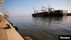 FILE - A cargo ship docks as its cargo is unloaded at Haifa's port, northern Israel, Oct. 12, 2020.