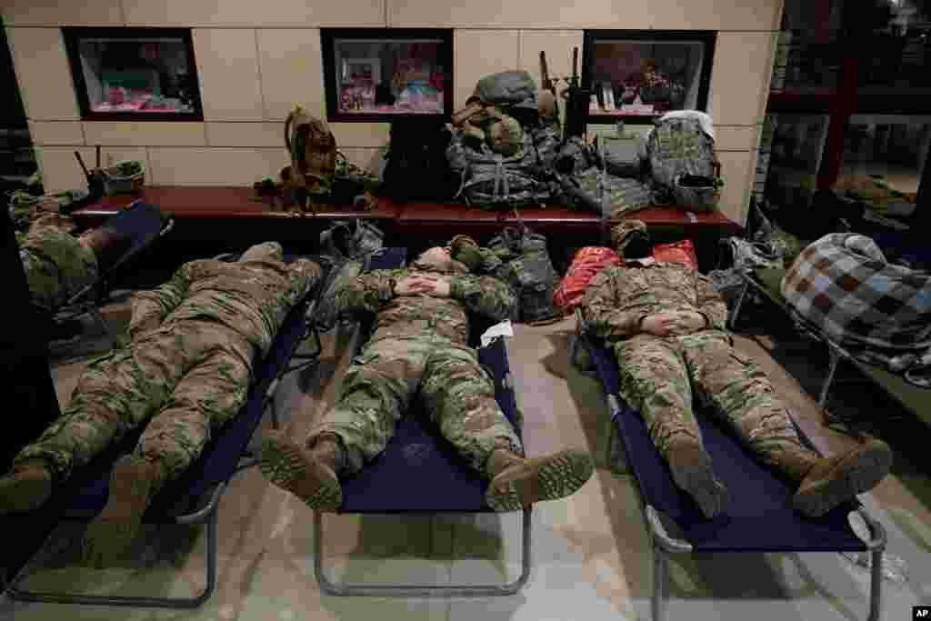 نیروهای گارد ملی که برای محافظت از مراسم تحلیف در ساختمان کنگره آمده اند، در سالن بازدیدکنندگان این ساختمان استراحت میکنند