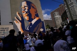 Demonstrators stop at the John Lewis Mural during a march for voting rights, Aug. 28, 2021, in Atlanta.