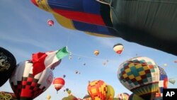 FILE - Thousands of spectators mingle among inflating hot air balloons at the 40th Albuquerque International Balloon Fiesta in Albuquerque, N.M., Oct. 2, 2011.