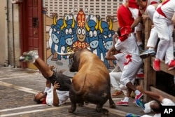 FILE - A reveler is gored by a Cebada Gago's ranch fighting bull during the running of the bulls in Pamplona, Spain.