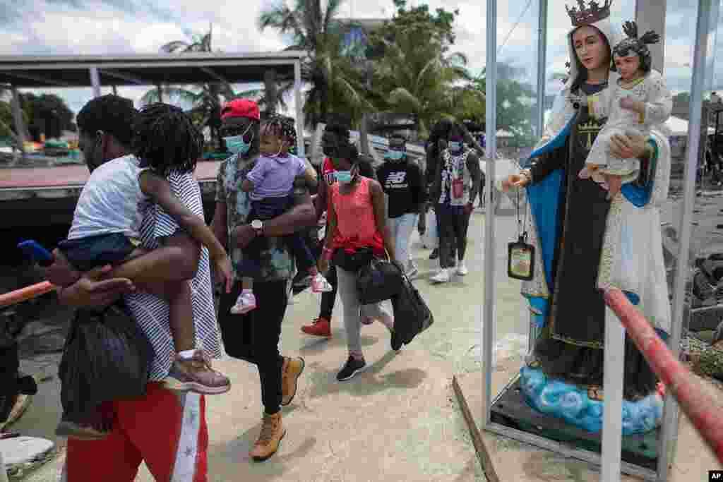 Migrantes haitianos pasan junto a la estatua de la Virgen María mientras abordan un barco hacia Capurganá.
