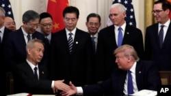 Predsjednik Donald Trump rukuje se sa kineskim vicepremijerom Liu Heom, nakon potpisivanja trgovinskog sporazuma u Bijeloj kući, 15. januar 2020. (Foto: AP/Evan Vucci)