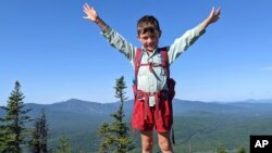 In this July 23, 2021 family photograph provided by Joshua Sutton, five-year-old Harvey Sutton raises his arms on a mountain top in Bigelow Preserve, Maine, while hiking the Appalachian Trail with his Mom and Dad.