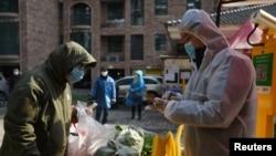 신종 코로나바이러스 감염증(COVID-19) 발원지인 중국 후베이성 우한에서 마스크를 착용한 시민이 단체주문한 채소를 받고 있다.