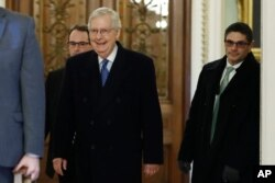 Senate Majority Leader Mitch McConnell, R-Ky., walks past the entrance to the Senate chamber as the arrives at his office at the Capitol, Jan. 22, 2020.