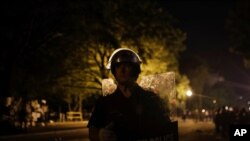 A. U.S. Park Police officer stands as police close the area around Lafayette Park near the White House after protesters tried to topple a statue of Andrew Jackson in the park in Washington, on Monday, June 22, 2020. (AP Photo/Maya Alleruzzo)
