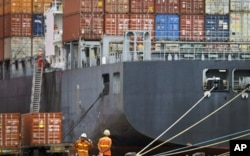 FILE - Workers rest near a loaded cargo ship at the Tianjin port in China.