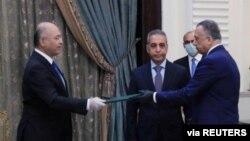Presiden Irak Barham Salih (kiri) menyerahkan dokumen kepada Perdana Menteri baru, Mustafa al-Kadhimi di Baghdad, Irak, 9 April 2020. (Foto: dok).