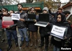 FILE - Kashmiri journalists display laptops and placards during a protest demanding restoration of internet service, in Srinagar, Nov. 12, 2019.