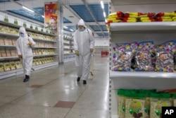 朝鲜平壤第一百货商店的员工在喷射消毒剂。(2020年12月28日)