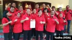 Pasangan calon dari PDIP, Gibran Rakabuming dan Teguh Prakosa (memegang kertas di depan), Jumat (17/7). Foto : VOA/ Yudha Satriawan