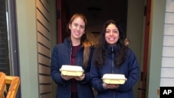 In this April 13, 2020 photo provided by Jay Peak Resort, Paula Davis, left, from Argentina, and Antonella Atto, from Peru, pose at the resort in Jay, Vt., with meals provided by The Belfry.