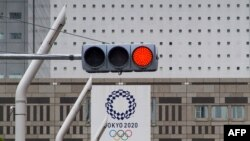 A red traffic light lights up on a street near the Tokyo Metropolitan Government Building displaying a banners of Tokyo 2020 Olympics Games in Tokyo on May 31, 2021.