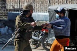 FILE - An Indian police officer detains a demonstrator during a protest after Friday prayers in Srinagar, March 5, 2021.