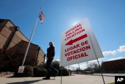 FILE - A sign points potential voters to an official polling location during early voting in Dallas, Feb. 26, 2020.