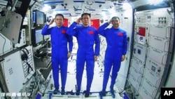Tiga astronaut China, dari kiri: Tang Hongbo, Nie Haisheng, dan Liu Boming memberikan hormat kepada Presiden China Xi Jinping saat melakukan telekonferensi dari stasiun antariksa (foto: dok).