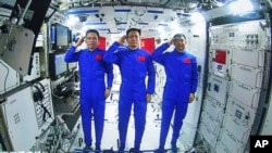 In this photo released by China's Xinhua News Agency, Chinese astronauts, from left; Tang Hongbo, Nie Haisheng, and Liu Boming salute from aboard China's space station core module Tianhe during a video conversation with Chinese President Xi Jinping,…
