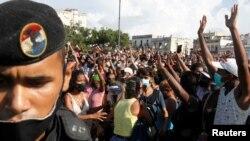 La gente reacciona durante las protestas contra y en apoyo del gobierno, en medio del brote de la enfermedad del coronavirus (COVID-19), en La Habana, Cuba, el 11 de julio de 2021.