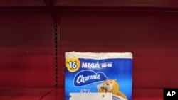 """FILE - A """"One Package per Household per Day"""" limit is requested for high-demand items like toilet paper, at the Gelson's Market in Los Feliz neighborhood of Los Angeles, March 26, 2020."""