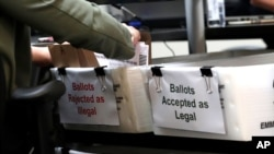 FILE - A Miami-Dade County Elections Department employee places a vote-by-mail ballot for the August 18 primary election into a box for rejected ballots at the Miami-Dade County Elections Department, in Doral, Florida, July 30, 2020.