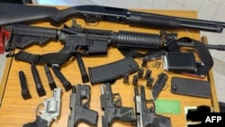 This image released by the Atlanta Police Department on March 25, 2021, shows weapons taken from a suspect arrested at a Publix Supermarket in Atlanta, Ga., March 24, 2021.