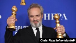 "Sam Mendes poses in the press room with the awards for best director, motion picture and best motion picture drama for ""1917"" at the 77th annual Golden Globe Awards at the Beverly Hilton Hotel on Sunday, Jan. 5, 2020, in Beverly Hills, Calif. (AP…"