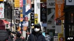 一位戴口罩的南韓女性走在首爾購物區街頭。