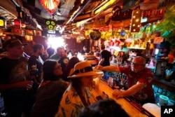 FILE - Patrons crowd into the tiny interior of the Tiki-Ti bar as it reopens on Sunset Boulevard in Los Angeles, July 7, 2021.